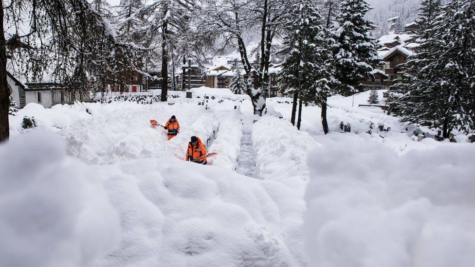 Two workers in fluorescent orange remove the snow off a path in Zermatt - it is easily up to their waist in places as they shovel it aside