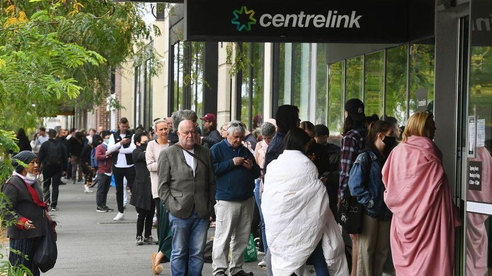 Hundreds of people queue outside an Australian government welfare centre, Centrelink, Melbourne