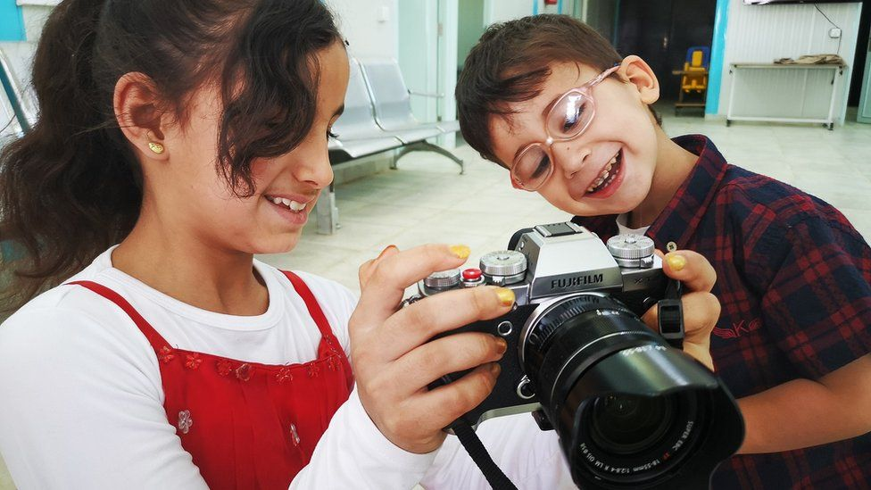 Refugee children with camera