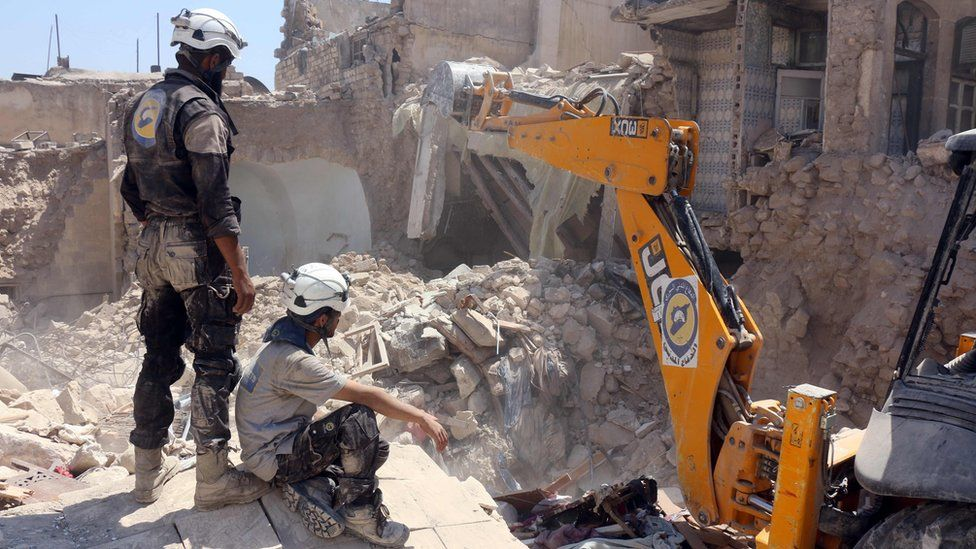 Syrian rescue workers, known as the White Helmets, look for survivors after a reported air strike in rebel-held Jallum district of Aleppo (20 August 2016)