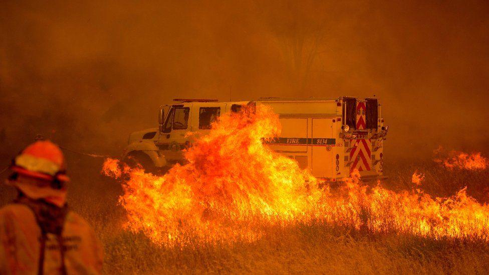 1 de julio: un vehículo de bomberos queda envuelto en llamas ante el paso de un incendio descontrolado que cruza la carretera cerca de Clearlake Oaks, en California el 1 de julio de 2018