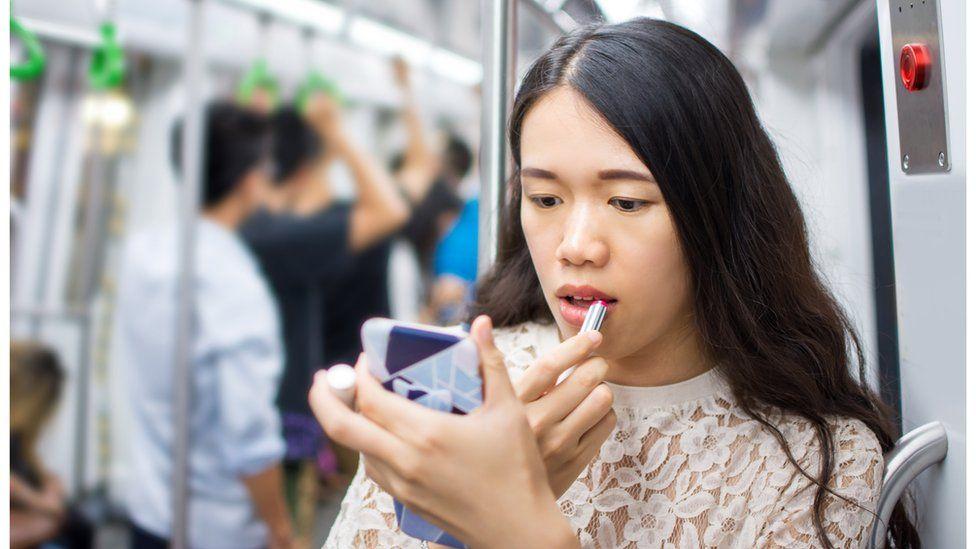 Woman applying make-up on the train