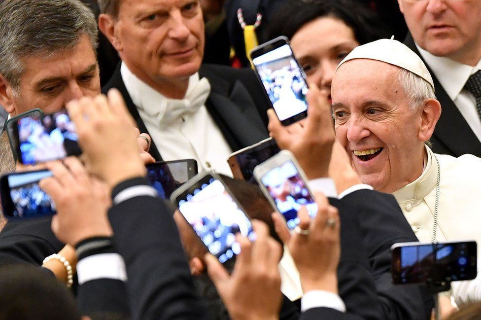 Pope Francis smiles as people take pictures on their mobile phones