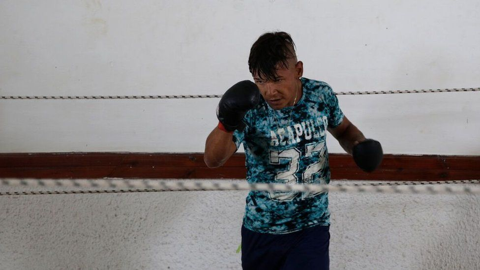 An inmate with boxing gloves practices in a ring