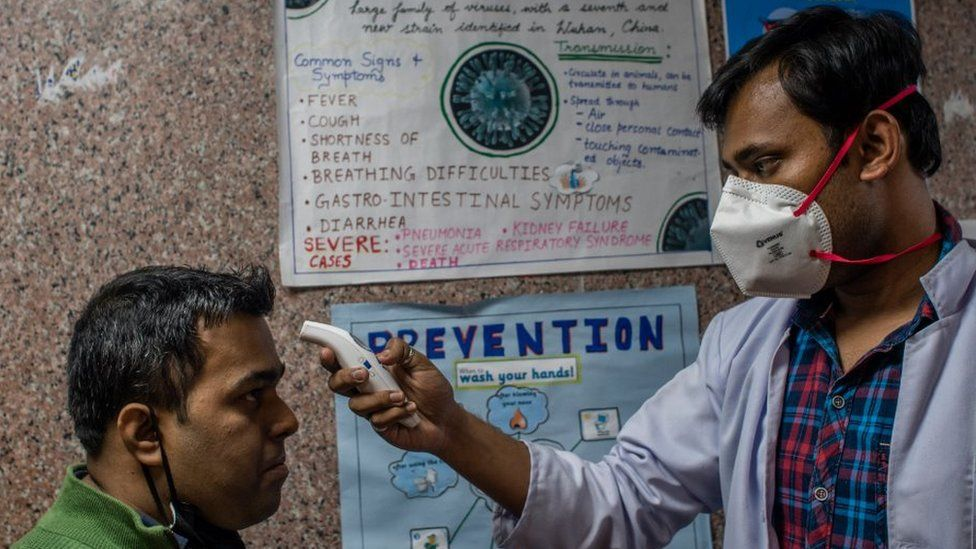 A doctor checks another man's temperature