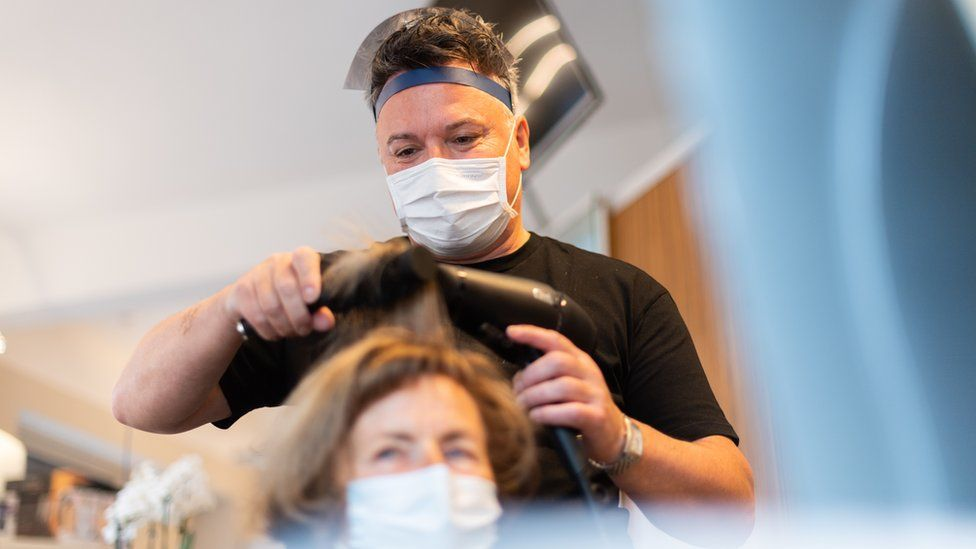 Hairdresser does the hair of a customer in his hairdressing studio, wearing a mouth guard and face shield.