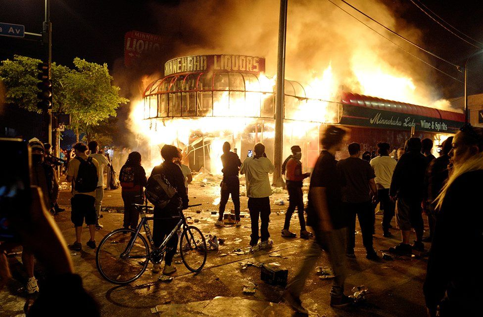 Protesters gather to watch a liquor store burning