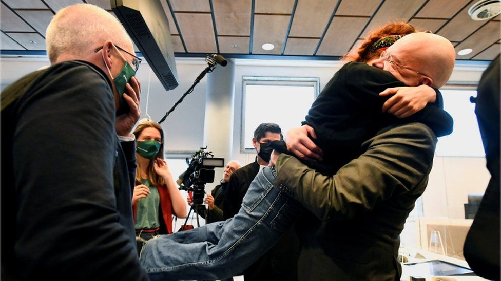 Environmental activists hug in court after a judge rules that Shell must cut its emissions