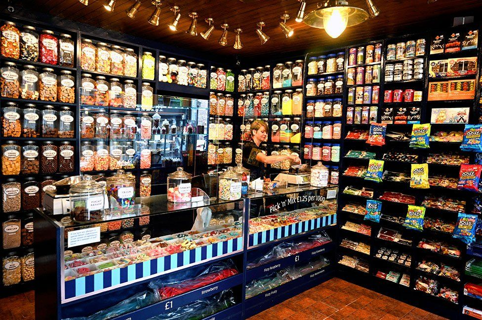 A shop worker stands behind a screen in a sweet shop