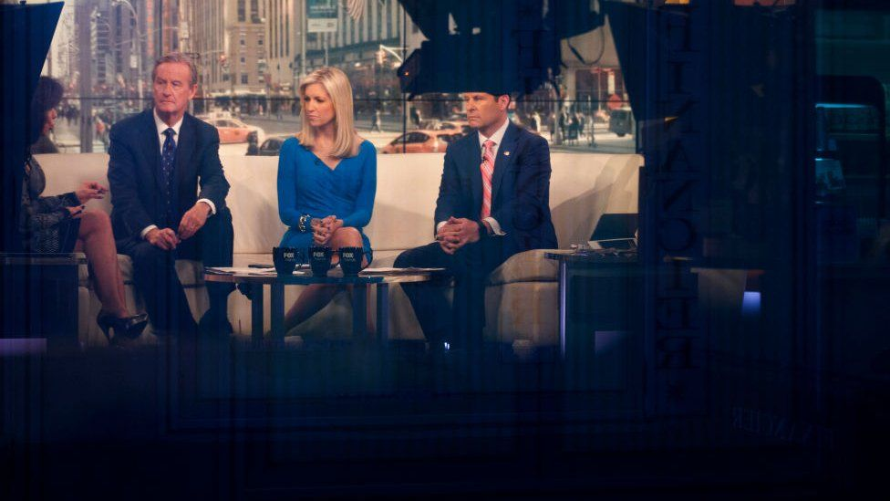 The hosts of Fox & Friends sit on set.