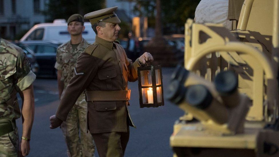 The lit candle being take to the Welsh National War Memorial, Cardiff