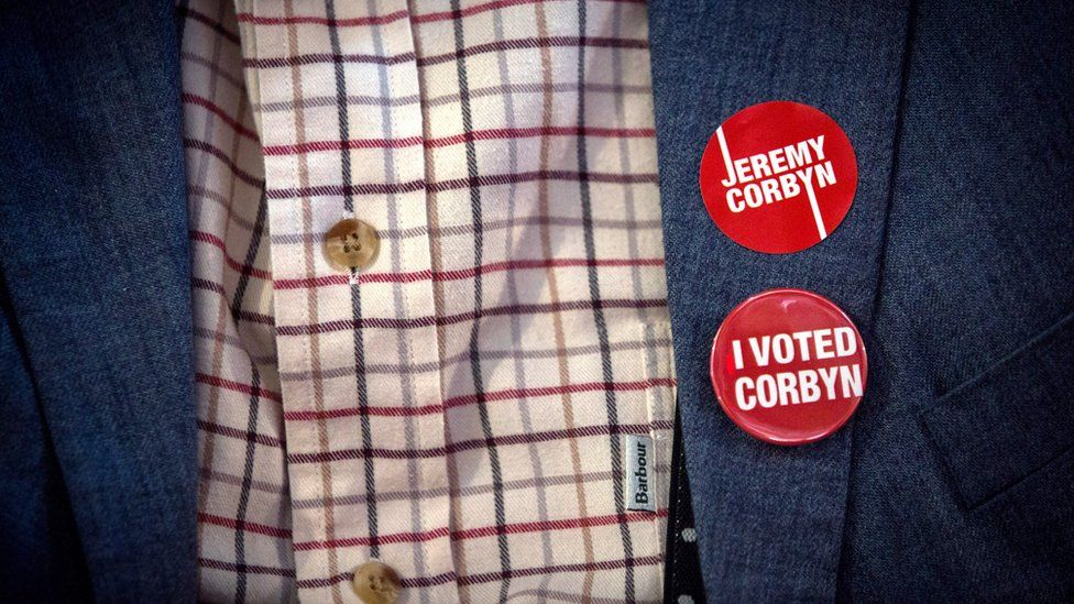 A supporter of Jeremy Corbyn wears badges on a jacket