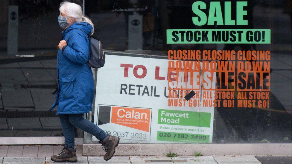Woman walking past a shop that has shut down