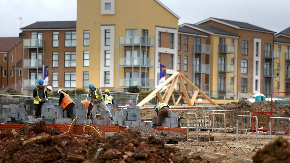 Construction workers building new houses on a housing development