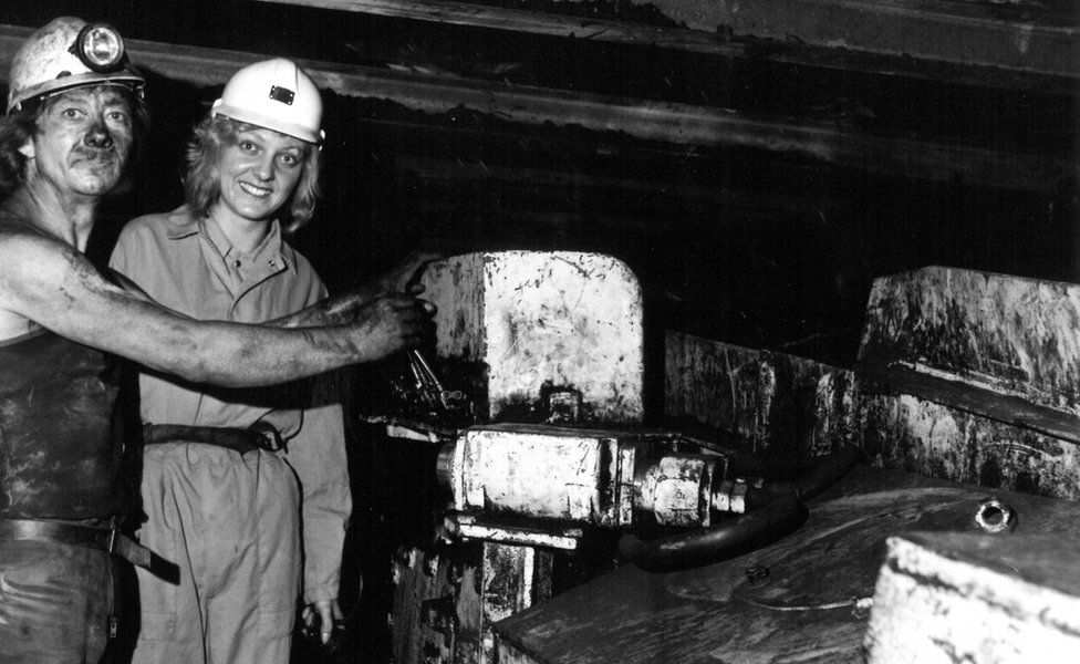 A man and a woman in a coal mine posing