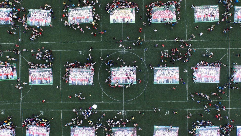 This picture taken on June 8, 2015 shows high school graduates putting together giant jigsaw puzzles made from their graduation photos on the playground after sitting the 2015 national college entrance examination