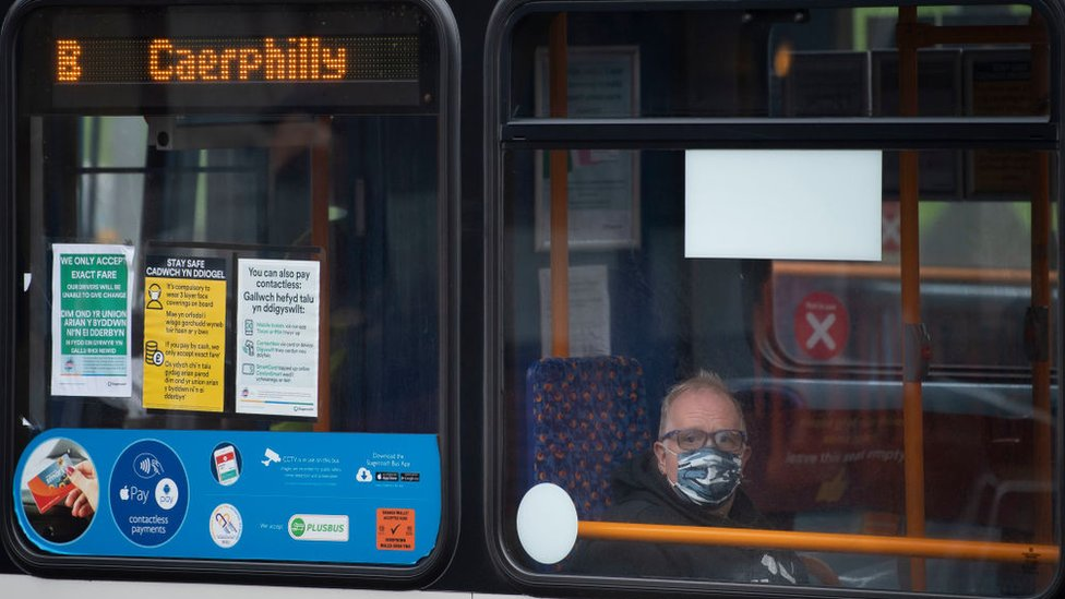 A bus in Caerphilly with a passenger wearing a mask