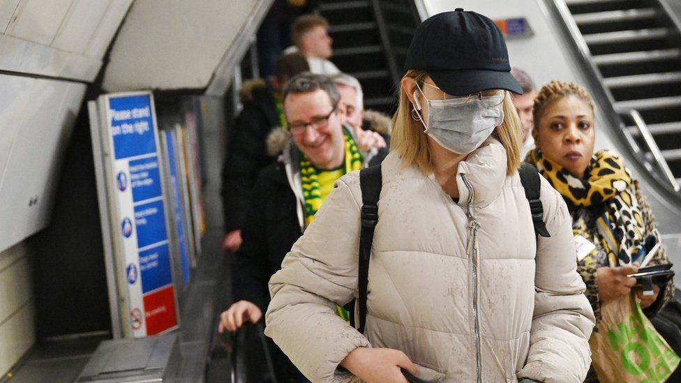 A woman wears a mask as she uses the Underground transport system in London, Britain, 04 March 2020