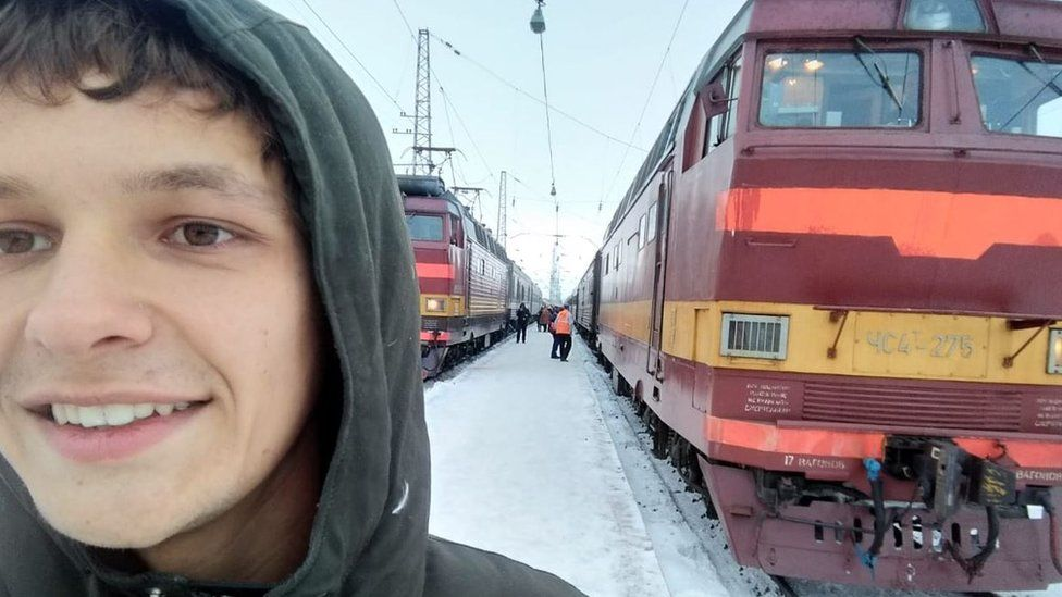 Elias Bohun standing outside trains in Siberia