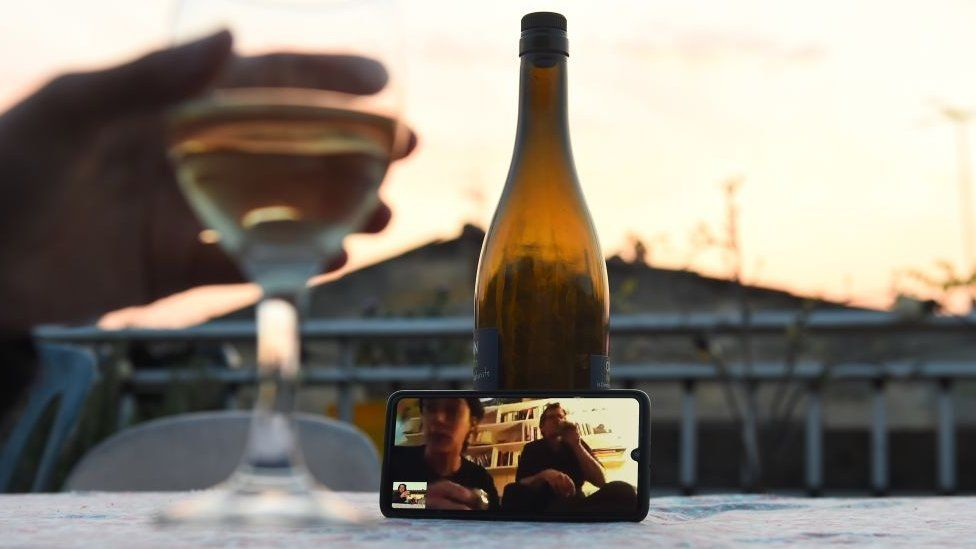 A woman shares a drink with friends via a video call