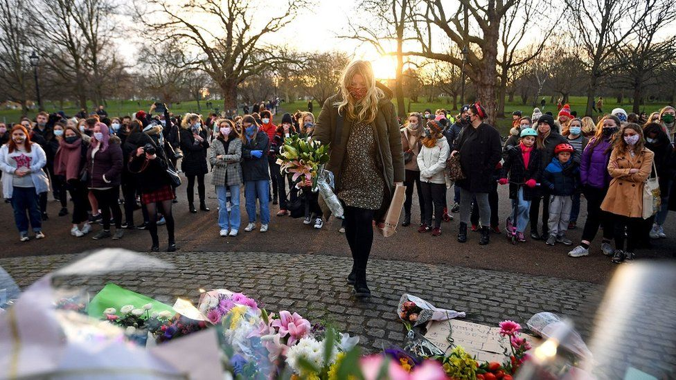 A woman leaves flowers at the bandstand on Clapham Common