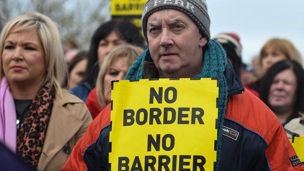 "Protestor holding a ""no border, no barrier"" sign"