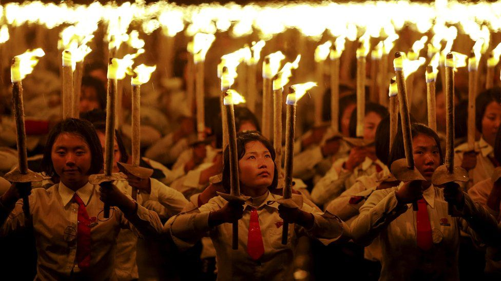 People holding torches during a performance held after the military parade for the 70th anniversary of the founding Workers' Party, Pyongyang, North Korea - Saturday 10 October 2015