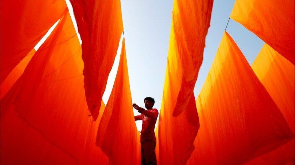 A worker dries fabrics after applying color at a dye factory in Narayanganj, Bangladesh, January 13, 2021.