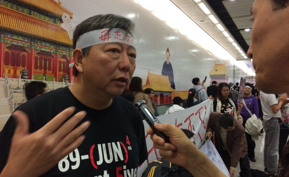 Lee Cheuk-yan talking to a reporter at a protest