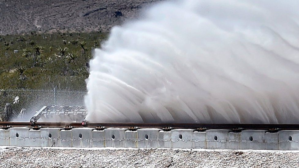 Sand is displaced as a test sled is slowed during the first test of the propulsion system at the Hyperloop One Test and Safety site