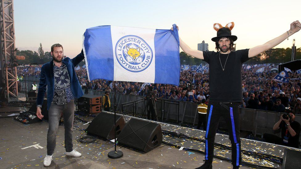 Band members hold LCFC flag