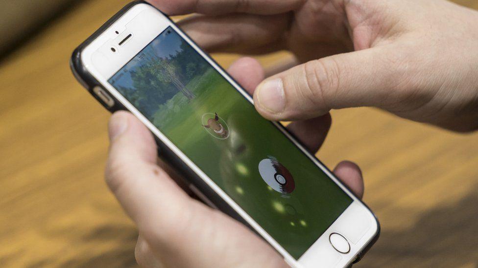 Man playing Pokemon on phone