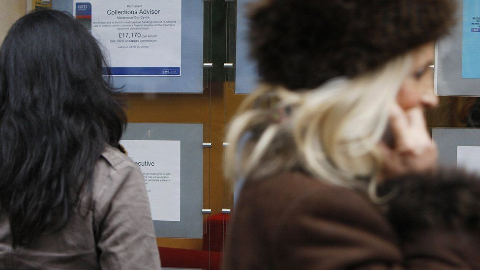 A woman looks at job advertisements in the window of a recruitment agency in Manchester