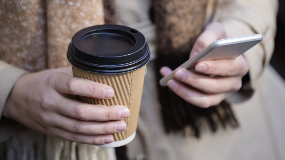 Woman holding coffee while using smartphone