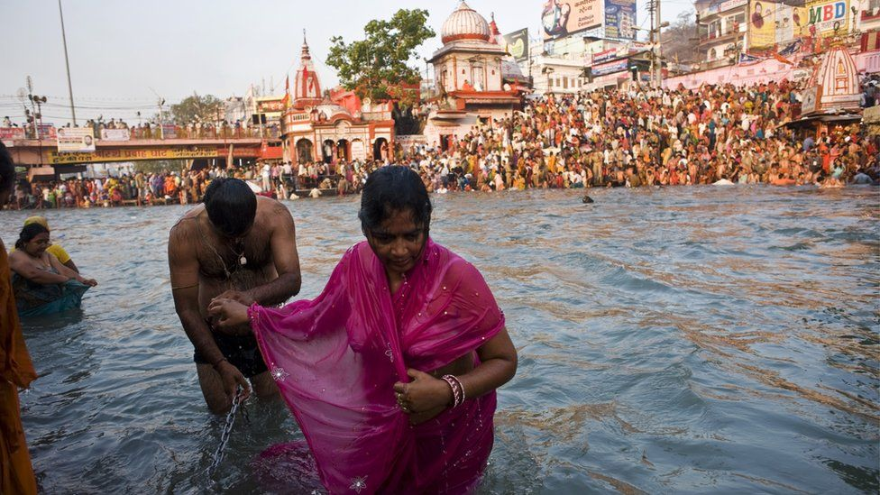 A Hindu couple holds hands after bathing in the river Ganges as deoveets crowd both banks during the Kumbh Mela festival in Haridwar on 13 April 2010