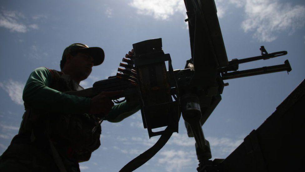 An Afghan government soldier behind a machine gun