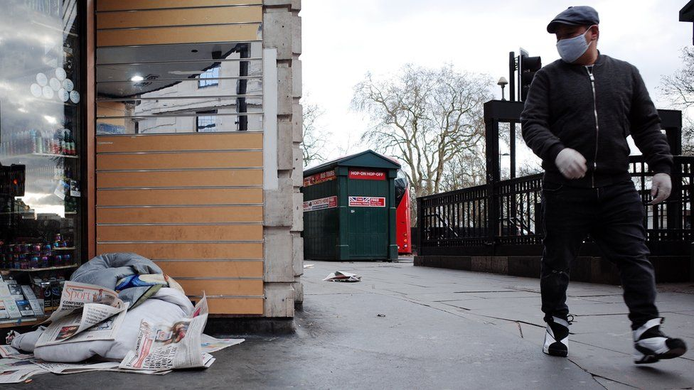 A man walks past a pile of a homeless person's belongings in a doorway at the Marble Arch end of Oxford Street in London