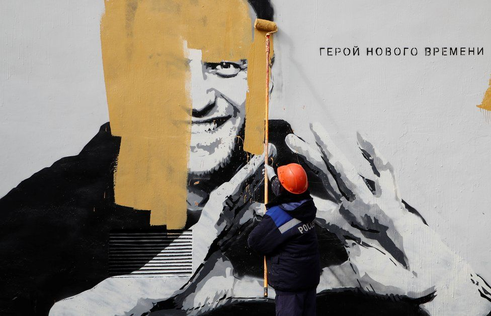 A worker paints over a mural depicting Alexei Navalny in St Petersburg