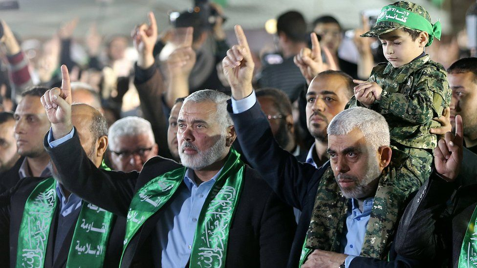 The new leader of Hamas movement in the Gaza Strip, Yahya Sinwar (R), holds on his shoulders the son of Mazen Fuqaha at a memorial (27 March 2017)