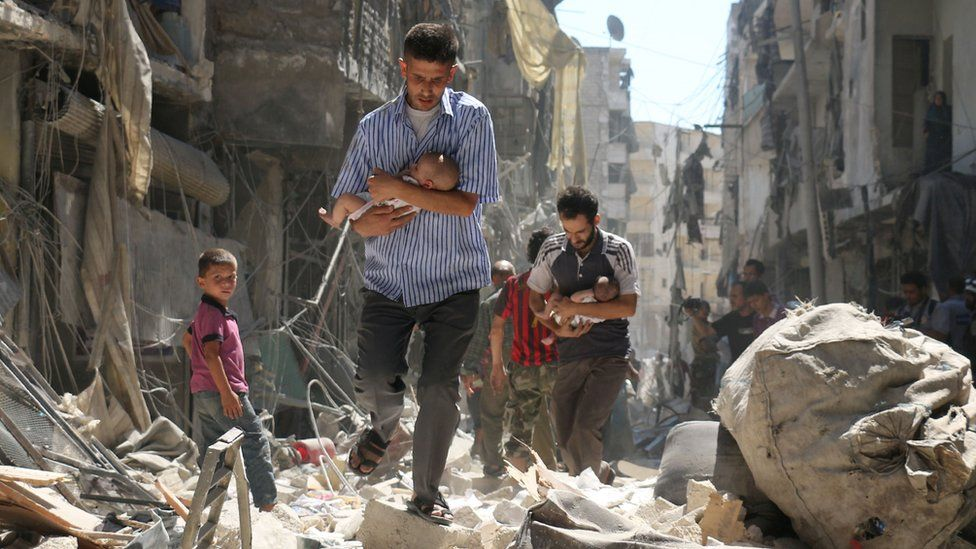 Syrian men carrying babies make their way through the rubble of destroyed buildings following a reported air strike on the rebel-held Salihin area of the northern city of Aleppo, on 11 September 2016