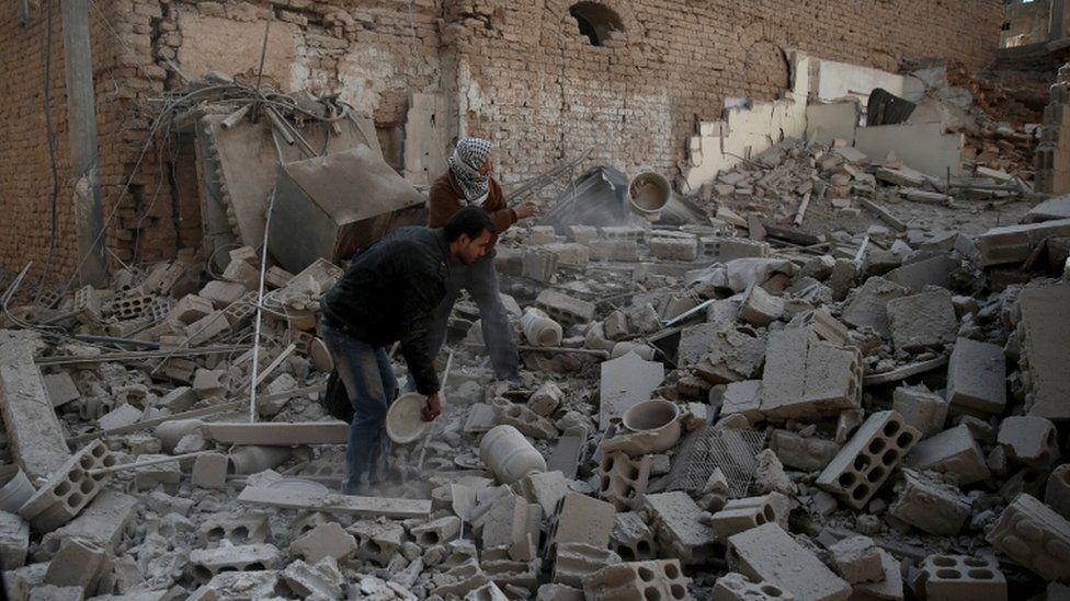 Men search for belongings at a site hit by missiles in the Douma neighbourhood of Damascus, Dec 2015
