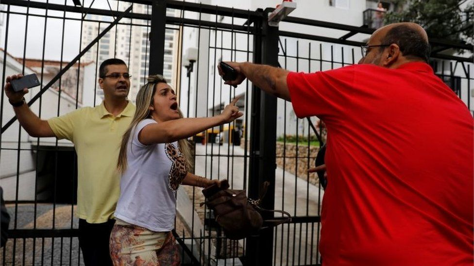 Supporters of Jair Bolsonaro (left) clash with a backer of the Workers' Party
