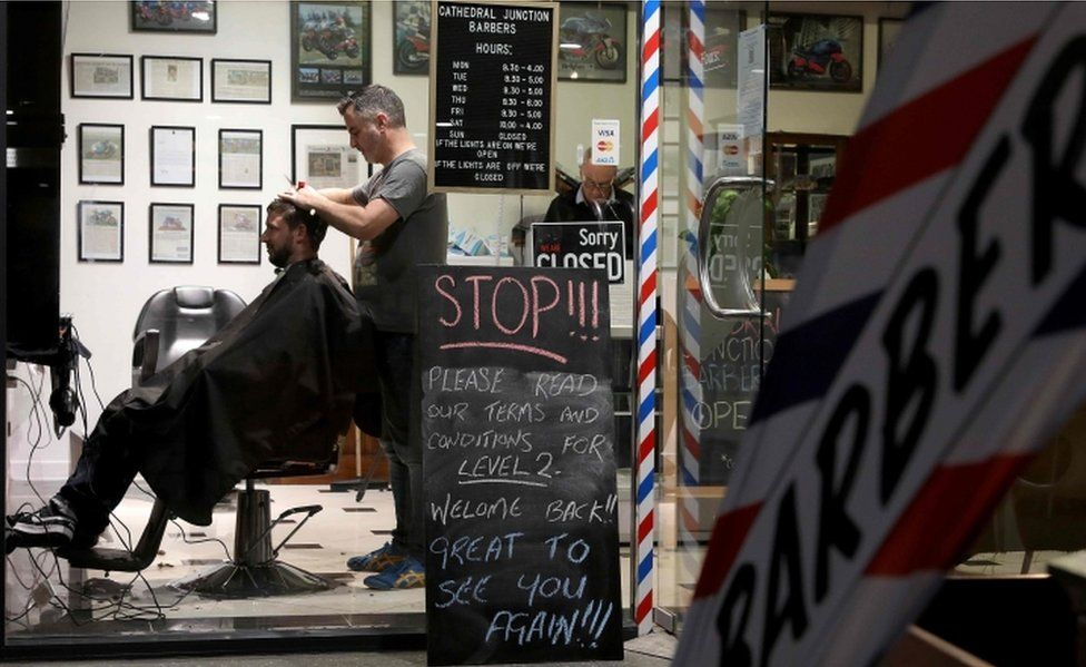 A barber cuts a customer's hair in Christchurch, on 14 May, 2020.