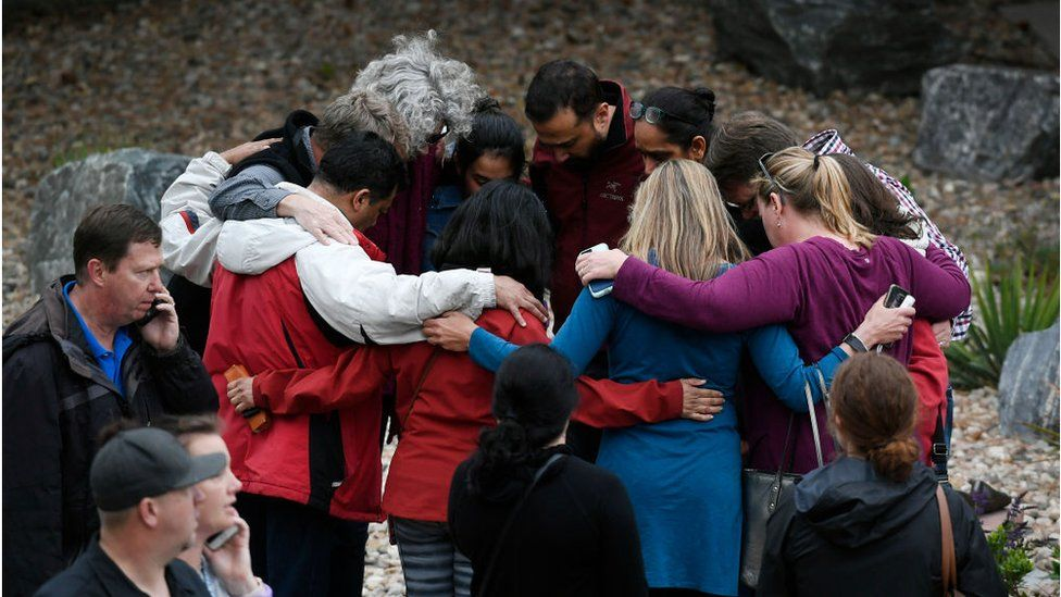 A group hugs one another as they wait to pick up their children after the shooting