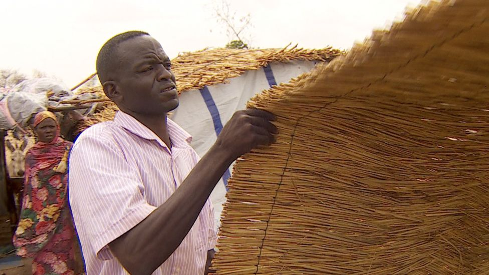 Khamis Mohamed Ishag Osman holds some thatching for a roof