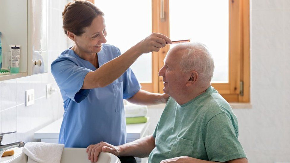 Home Caregiver with senior man in bathroom - stock photo