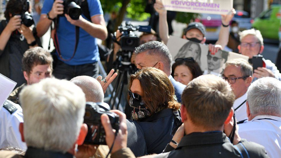 US actor Johnny Depp (C) gestures as he arrives to attend on day ten of his libel trial against News Group Newspapers (NGN), at the High Court in London, on July 20, 2020.