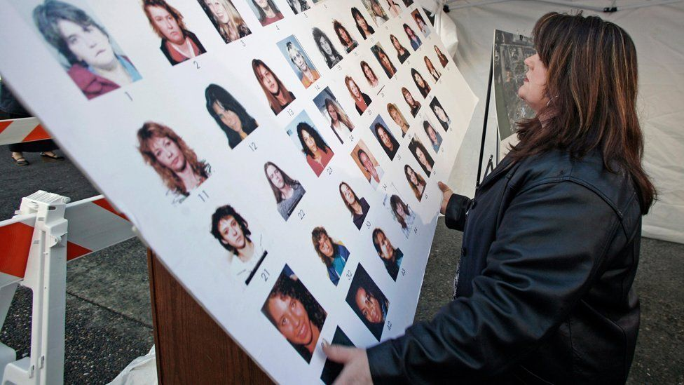 Court official Kathryn Quon puts up a poster of missing women outside the court where the trial for accused serial killer Robert Pickton, 2007