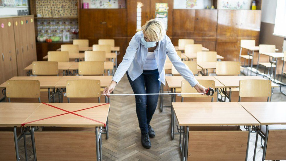 Woman in face mask measuring space between desks