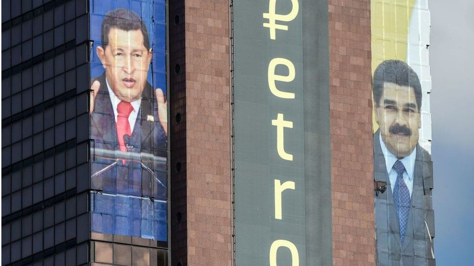 The logo of the 'Petro' is displayed next to images of former Venezuelan president Hugo Chavez and current President Nicolas Maduro on a building in Caracas
